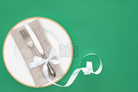 Photo for Elevated view of plate with fork and knife wrapped by festive ribbon isolated on green - Royalty Free Image