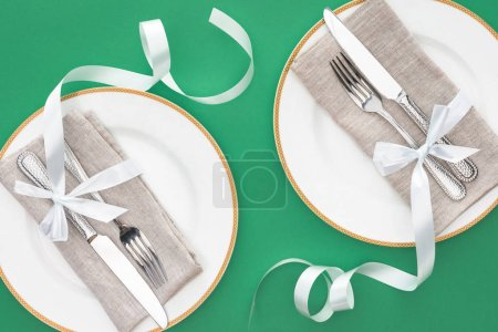 flat lay with forks and knives wrapped by festive ribbons on plates isolated on green