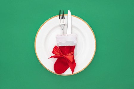 Photo for Top view of fork and knife in christmas sock on plate isolated on green - Royalty Free Image