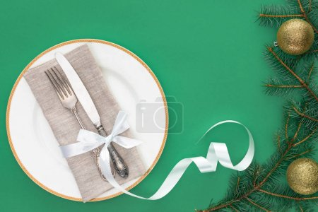 flat lay with fork and knife wrapped by festive ribbon on plate near evergreen tree branches with christmas balls isolated on blue