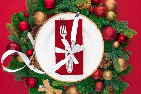 view from above of fork and knife wrapped by festive ribbon on plate surrounded by evergreen tree branches with christmas balls isolated on red