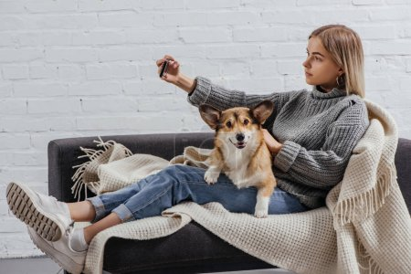 beautiful girl taking selfie with corgi dog on sofa