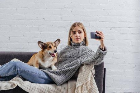 Photo pour Jolie fille prenant selfie avec chien corgi drôle sur smartphone - image libre de droit