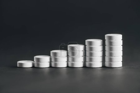 close up view of arranged stacks of white pills placed in rows on grey