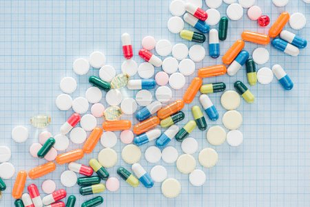 Photo for View from above of arranged various colorful pills on blue checkered surface - Royalty Free Image