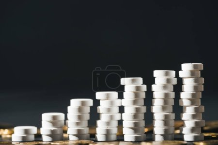 close up view of arranged stacks made of white pills near pile of coins on grey