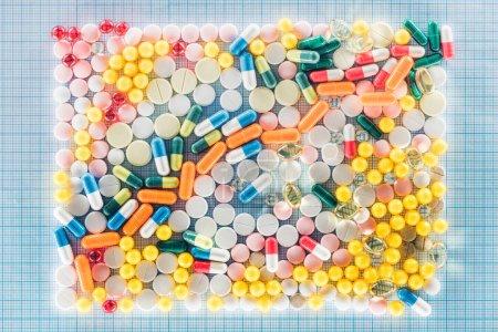 Photo pour Couché plat avec rectangle composé de diverses pilules colorées sur une surface à carreaux bleus - image libre de droit