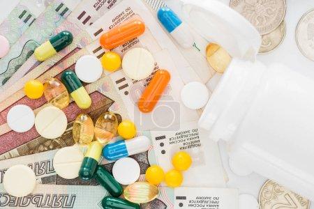 vista superior de varias píldoras de colores y rublos rusos en la superficie