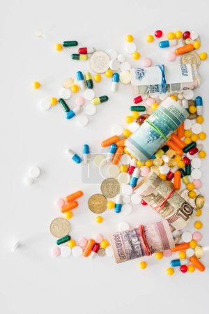 top view of colorful various pills and russian rolled banknotes on surface
