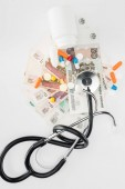 elevated view of stethoscope, colorful various pills and russian banknotes on white surface