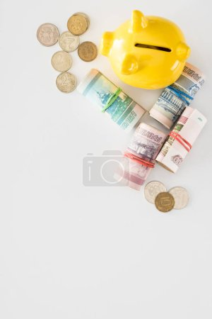 elevated view of yellow piggy bank and various rolled russian banknotes with coins on white surface