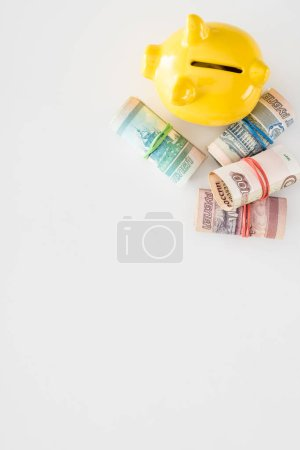 view from above of yellow piggy bank and various rolled russian banknotes on white surface