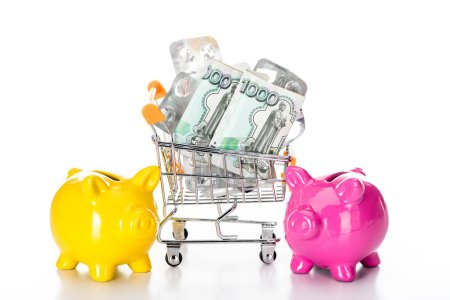 trolley cart with russian cash money and empty pills packages near pink piggy bank and colorful pills isolated on white