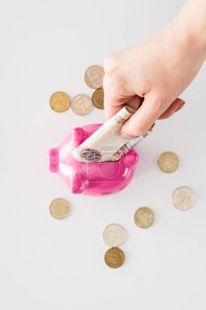 cropped image of woman putting russian banknote into pink piggy bank surrounded by coins on white surface