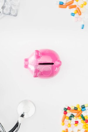flat lay with pink piggy bank surrounded by colorful various pills, stethoscope and empty pills packages on white surface