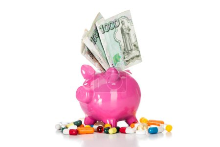 close up shot of pink piggy bank with russian banknote surrounded by various colorful pills isolated on white