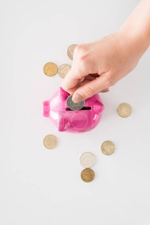 cropped image of woman putting coin into pink piggy bank on white surface
