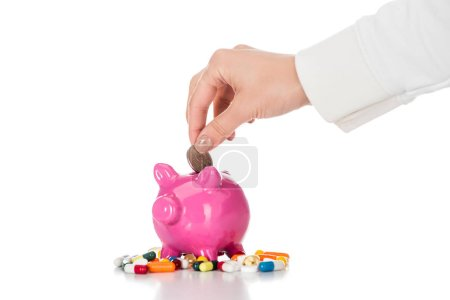 cropped image of woman putting coin into pink piggy bank surrounded by colorful pills isolated on white