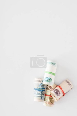 top view of various russian rolled banknotes on white surface