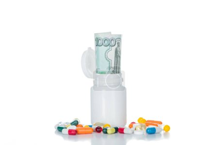 close up shot of pill bottle with russian cash money surrounded by colorful different pills isolated on white
