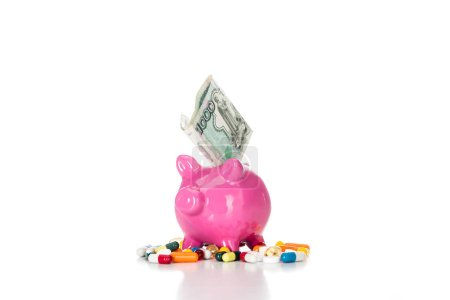 pink piggy bank with russian banknote surrounded by various colorful pills isolated on white