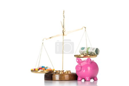 close up view of pink piggy bank near scales with various colorful pills and russian cash money isolated on white
