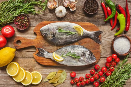 Photo for Elevated view of raw fish on wooden board surrounded by ingredients on table - Royalty Free Image
