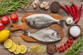 food composition with raw fish on wooden board surrounded by ingredients on table