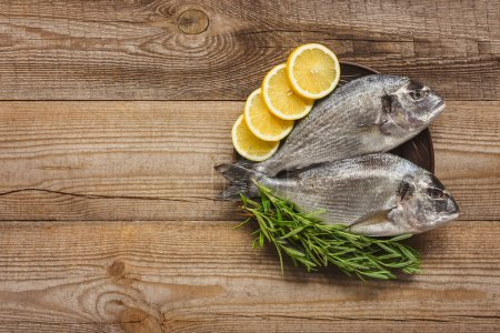 top view of raw fish with lemon and rosemary on wooden table