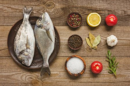 Photo for View from above of plate with uncooked fish near arranged ingredients on wooden table - Royalty Free Image
