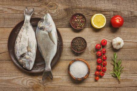 Photo pour Vue de plaque avec des poissons crus près ingrédients disposés sur une table en bois - image libre de droit