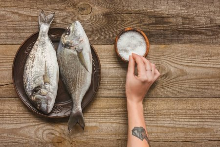 cropped image of tattooed woman salting uncooked fish on wooden table