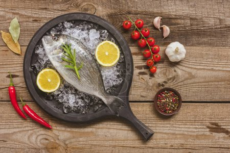 Photo for View from above of tray with uncooked fish near ingredients on table - Royalty Free Image