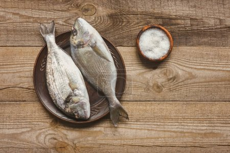 top view of salt and plate with uncooked fish on wooden table