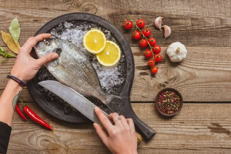 Photo for Cropped image of tattooed woman cutting raw fish by knife on wooden table - Royalty Free Image