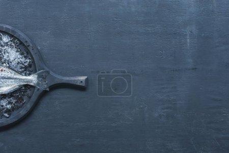 Photo pour Vue du bac avec des poissons crus sur table - image libre de droit