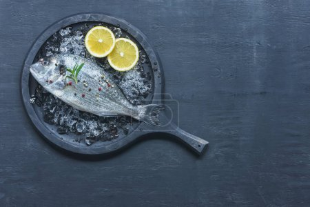 Photo for Top view of tray with uncooked fish with lemon and rosemary on table - Royalty Free Image
