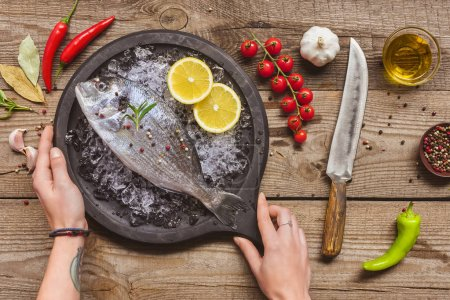Photo for Cropped image of tattooed man taking tray with uncooked fish on table with ingredients - Royalty Free Image
