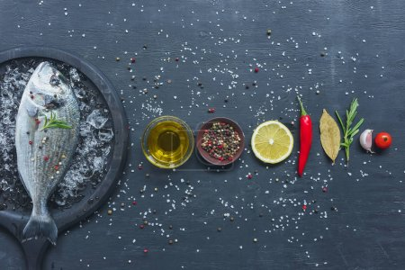 Photo for Elevated view of arranged ingredients near tray with uncooked fish on black table - Royalty Free Image