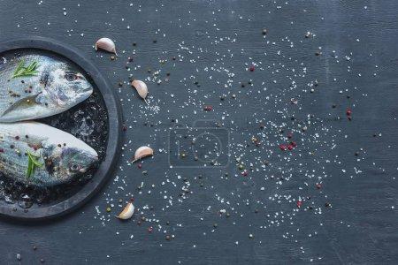 Foto de Lay Flat con pescado, ajo y Romero en mesa negro cubierto por sal y pimienta - Imagen libre de derechos