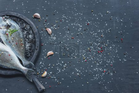 Photo pour Vue du poisson cru wit romarin dans barre des tâches sur un tableau noir à l'ail - image libre de droit
