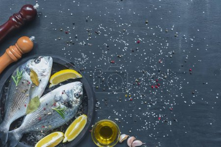 top view of raw fish with ingredients in tray on black table covered by salt and pepper