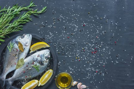 Photo for View from above of raw fish with lemon, bay leaves and rosemary in tray on black table covered by salt and pepper - Royalty Free Image