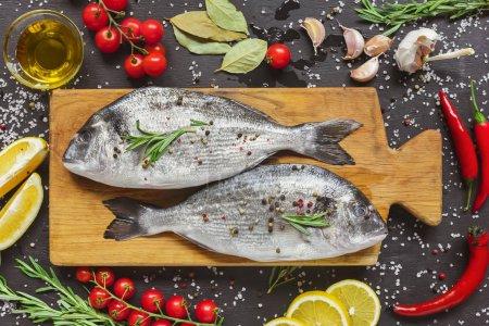 Photo pour Vue d'en haut la composition alimentaire avec poisson cru et ingrédients sur tableau noir - image libre de droit