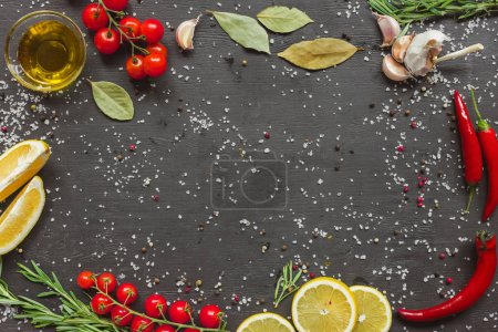 top view of cherry tomatoes, garlic, lemon, rosemary, chili and olive oil in glass on black table