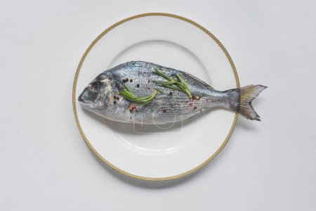 Photo pour Vue de dessus du poisson non cuit avec du romarin et de poivre sur plaque - image libre de droit