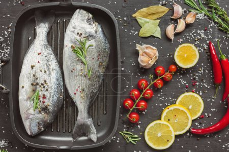 elevated view of uncooked fish near ingredients on black table