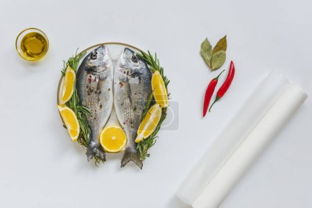 top view of baking paper, olive oil and fish decorated by rosemary and lemon on plate