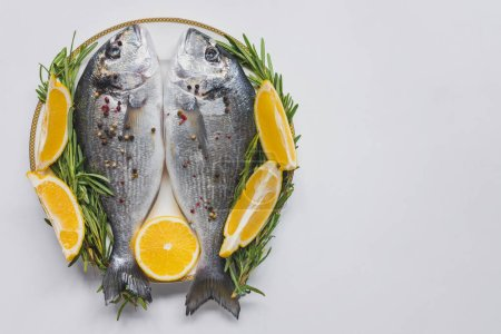Photo for View from above o fish decorated by rosemary and lemon on plate - Royalty Free Image
