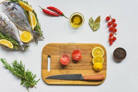 Foto de Vista superior de pescado crudo y varios ingredientes en mesa blanca - Imagen libre de derechos